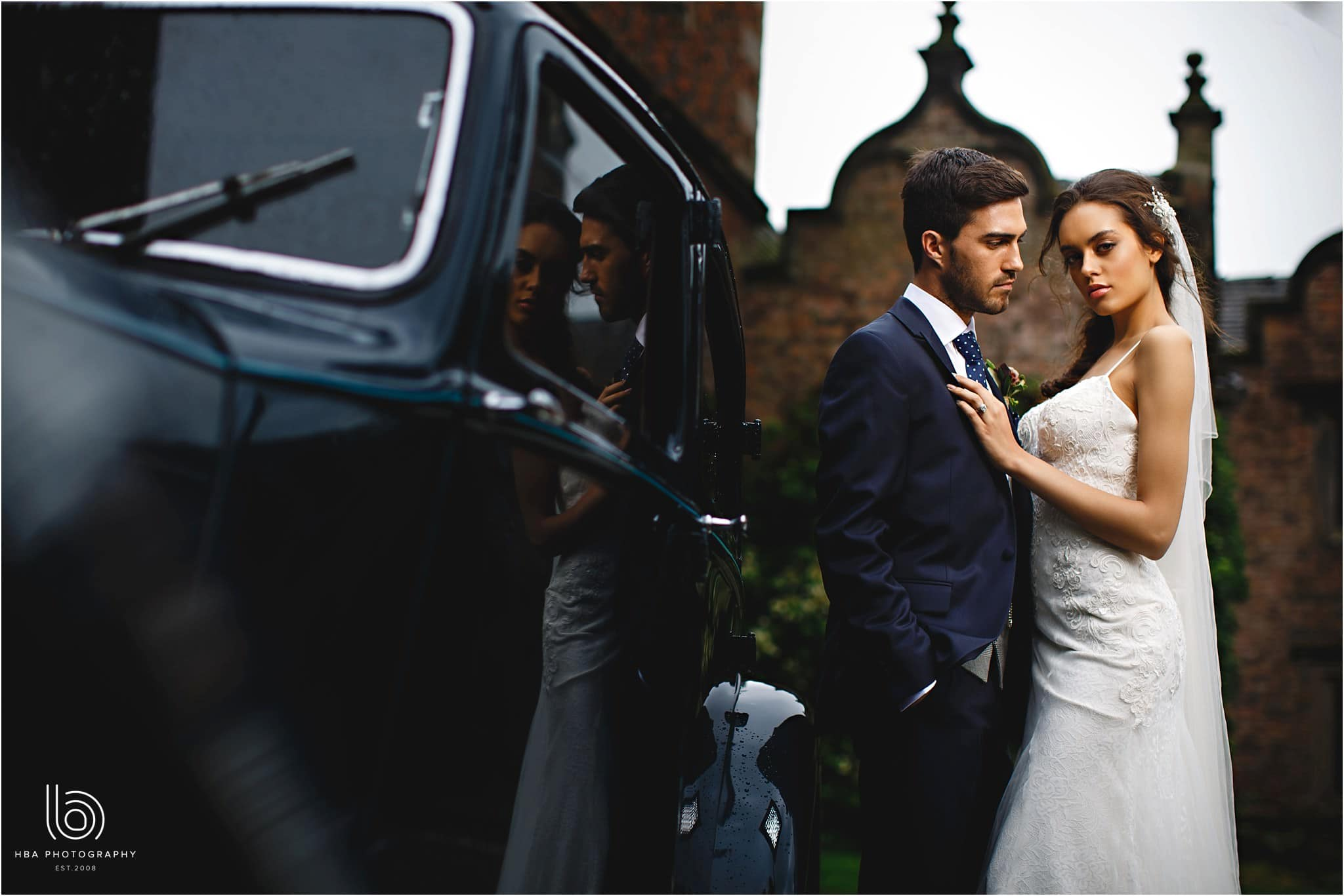 the bride and groom stood by the wedding car at Dorfold Hall