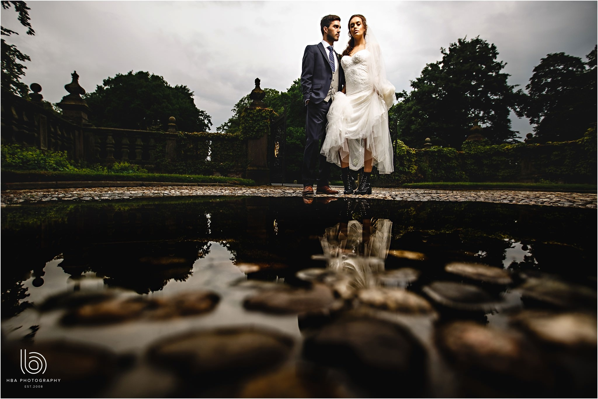 the brid eand groom stood by water at Dorfold Hall