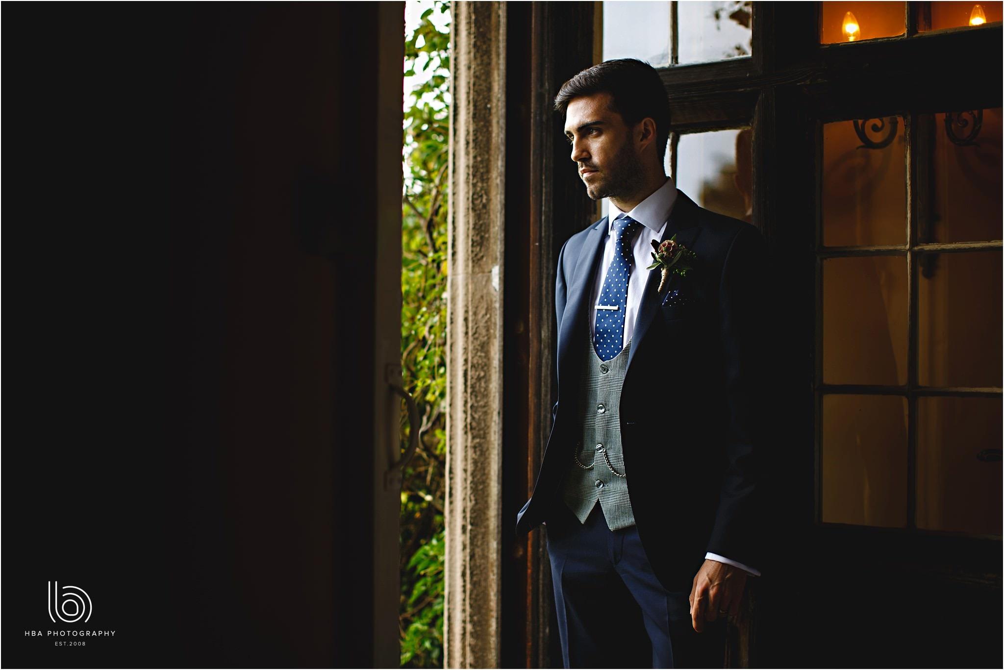 the groom stood in the doorway looking cool in his suit