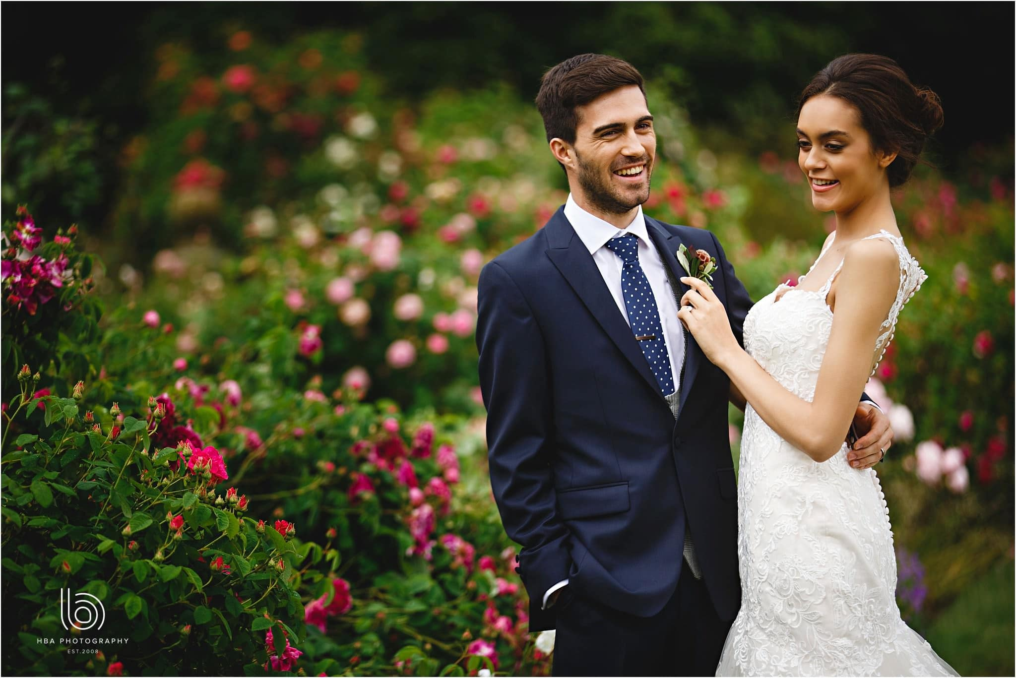 the bride and groom laughing in the rose garden