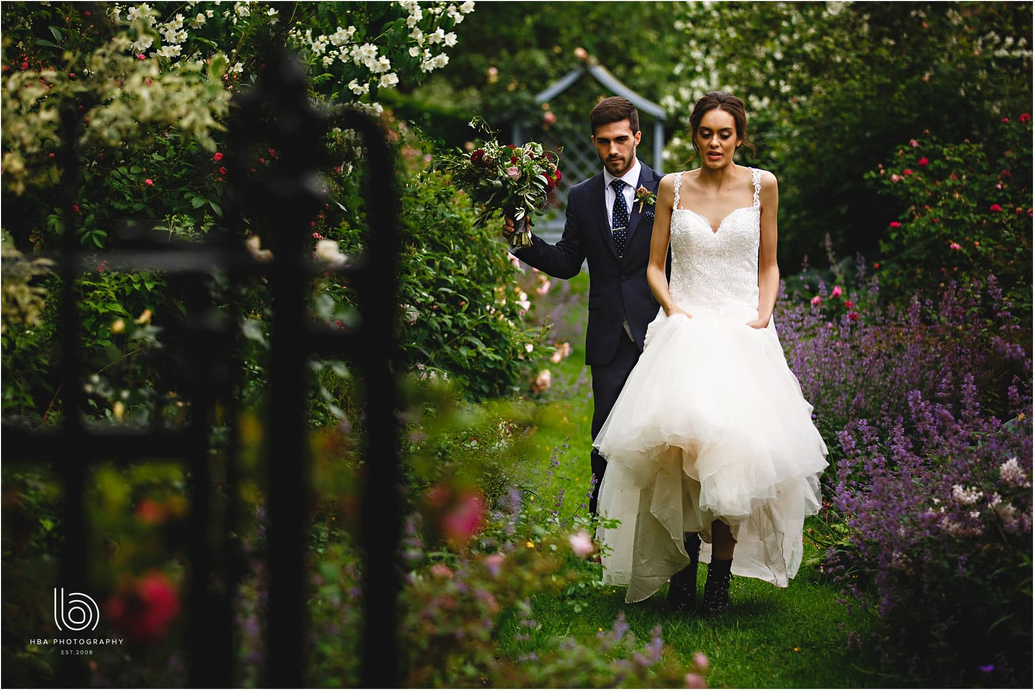 the bride and groom walking out of the dorfold Hall gardens