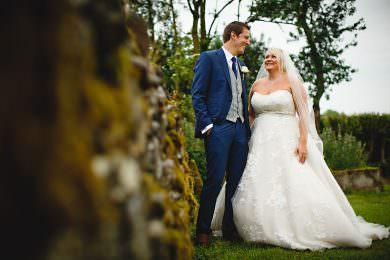 The bride and groom in a blue suit stood near a wall at The Knockerdown Cottages
