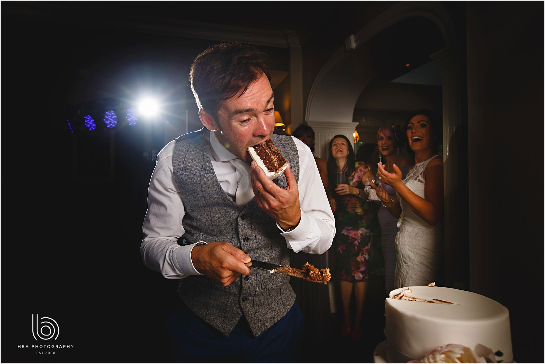 the groom eating the wedding cake