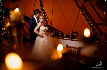 the bride & groom inside the tipi cuddling