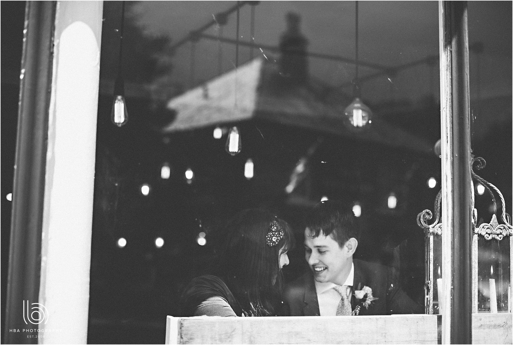 the bride & groom sitting in a cafe window