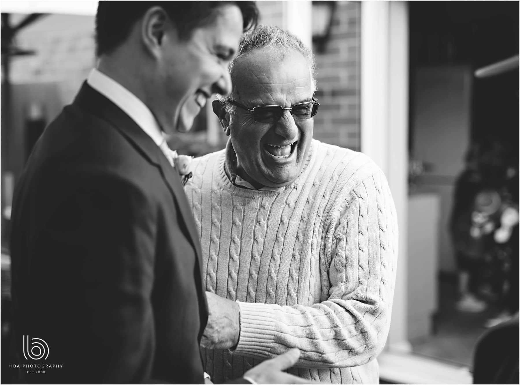 the father of the bride laughing with the groom