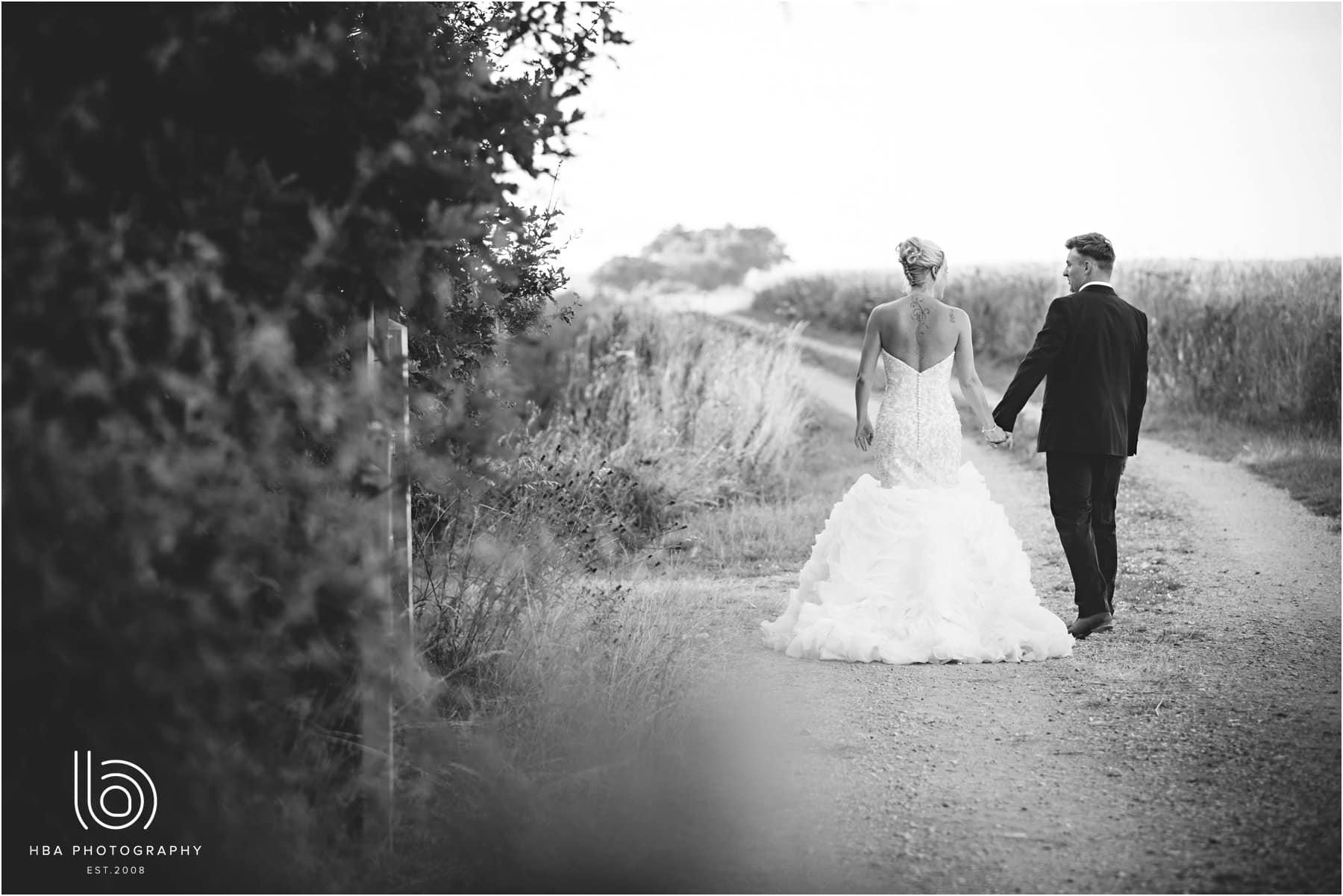 the bride & Groom walking down a path