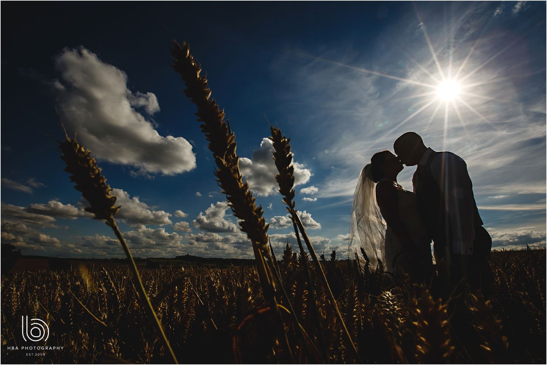 the bride & groom in silhouette with a sun star