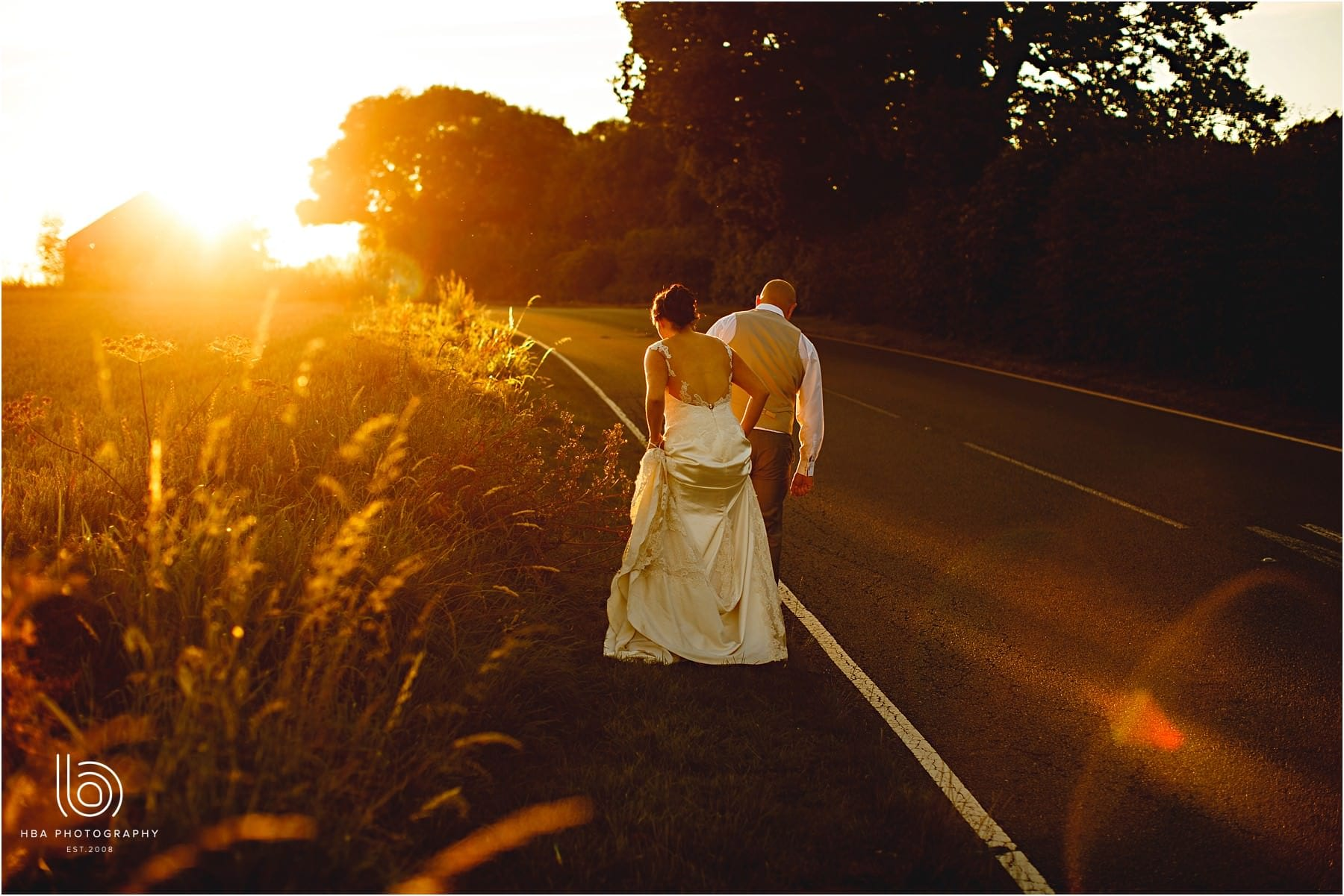 the bride & groom walking up the road in the golden sun