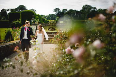 the bride and grom at Tissington Hall waliking through the rose gardens