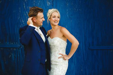 The bride and groom stood in front of blue doors at Bassmead Manor