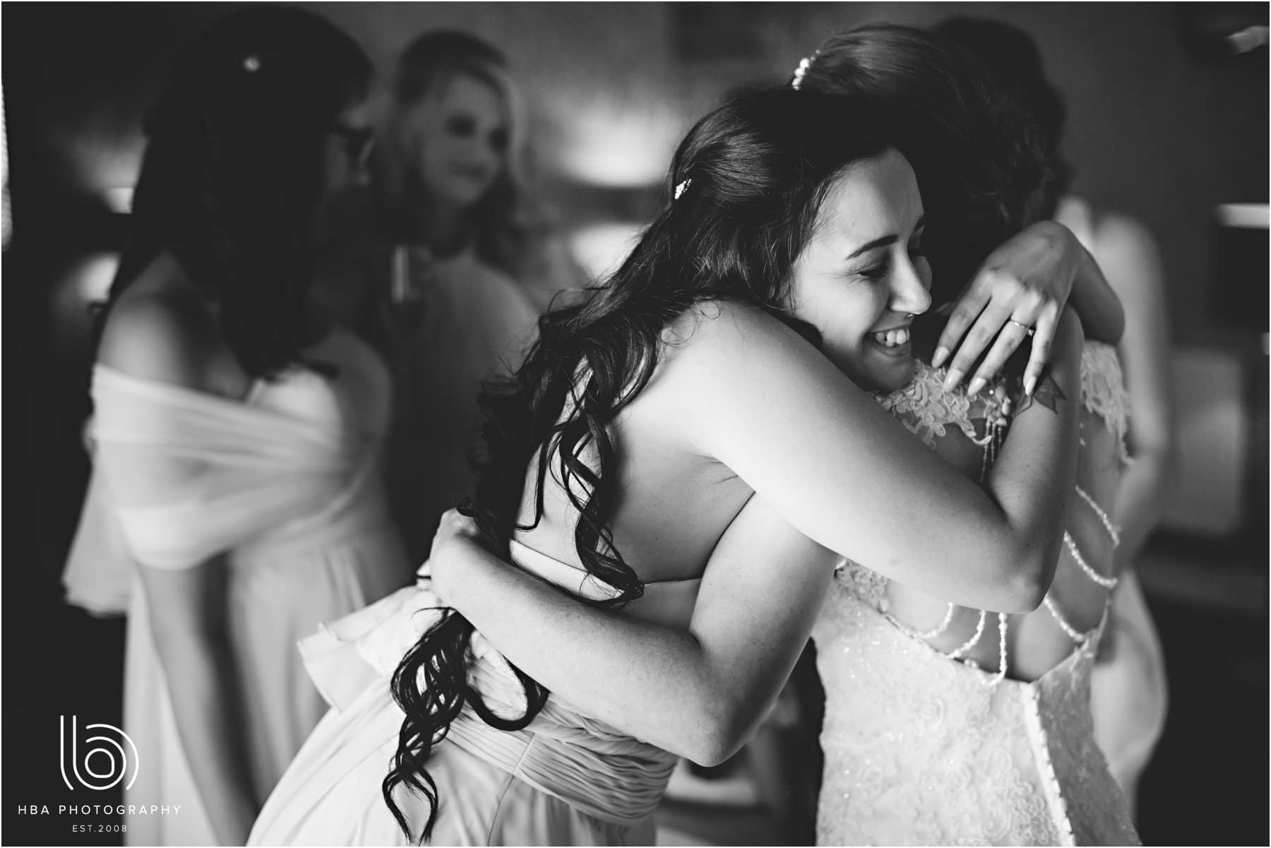 the bridesmaids hugging the bride