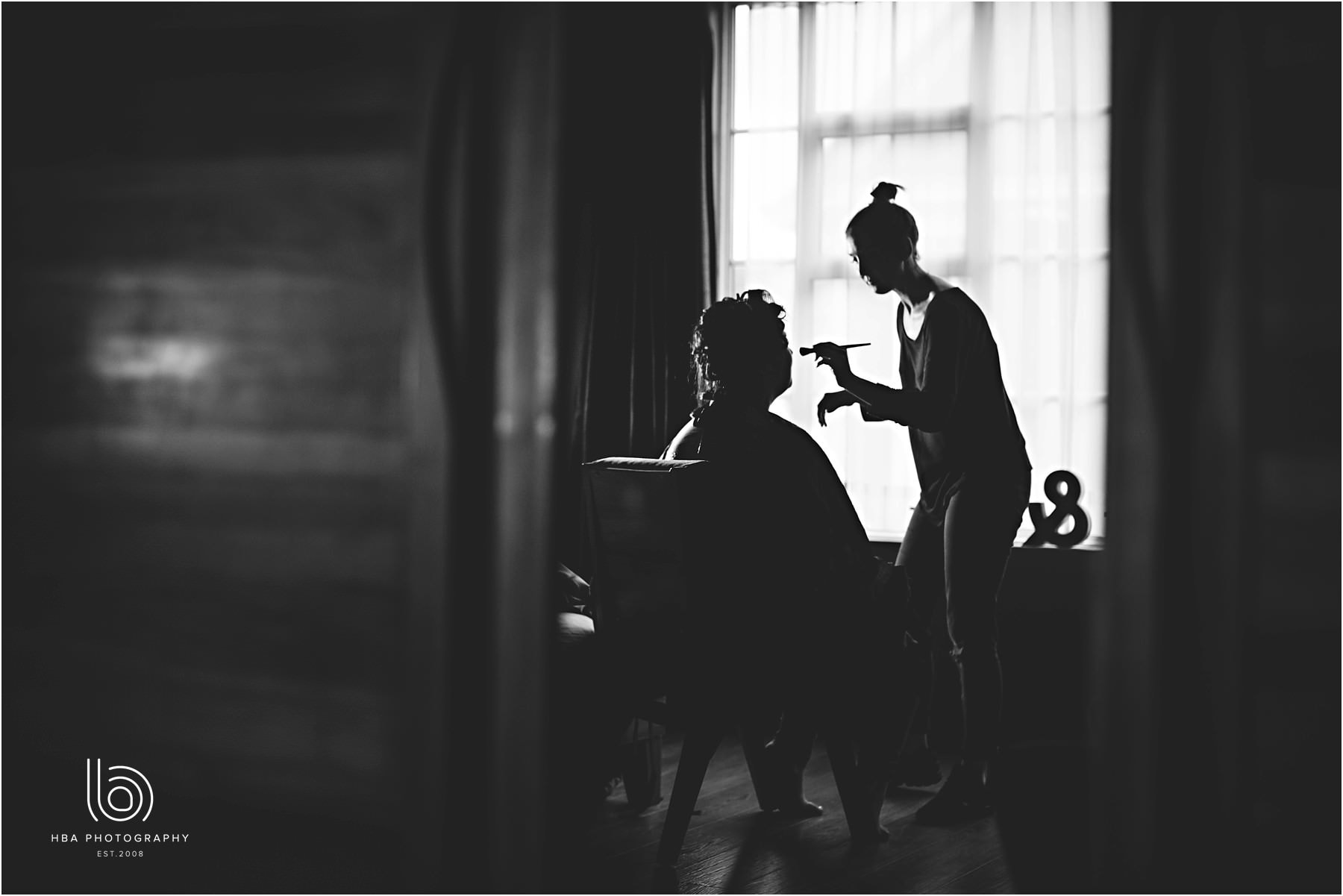 a black and white photo of the bride having her makeup done