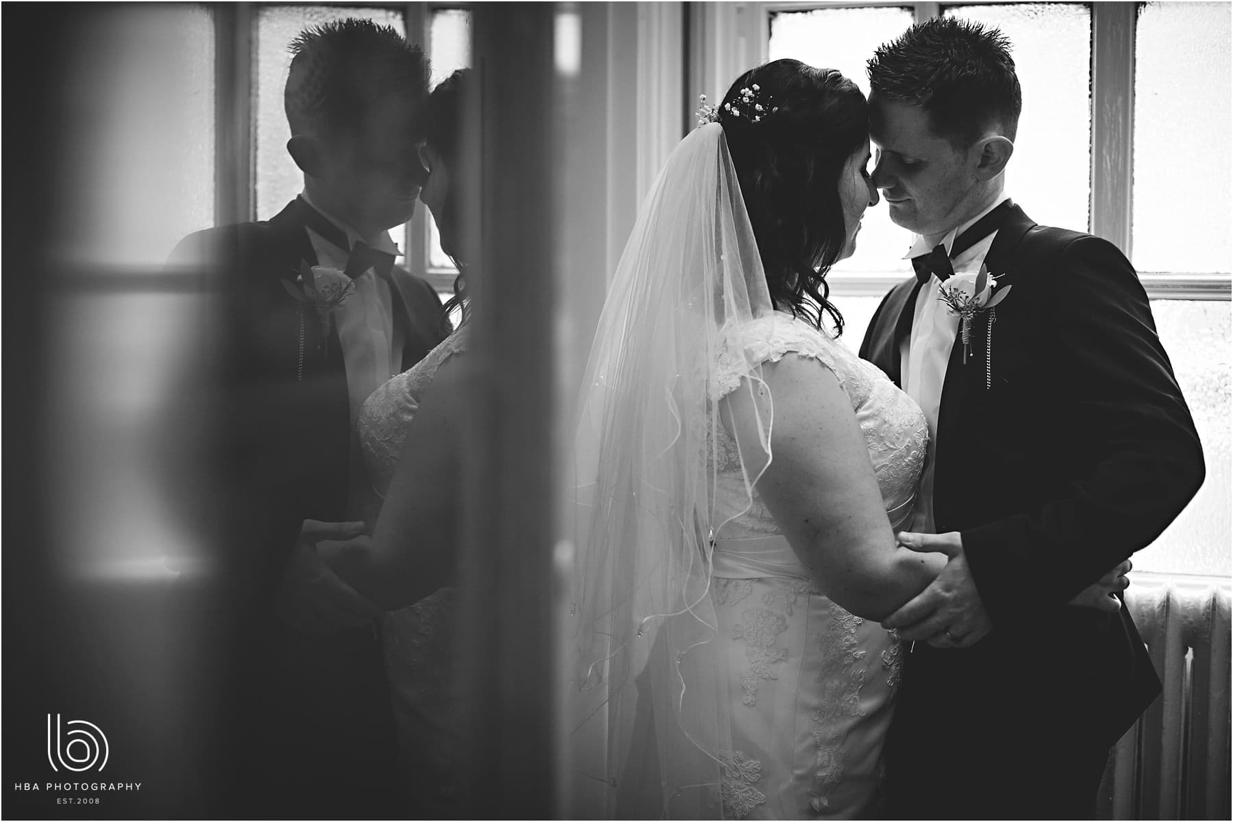 a black and white photo of the bride and groom together with a reflection on the wall