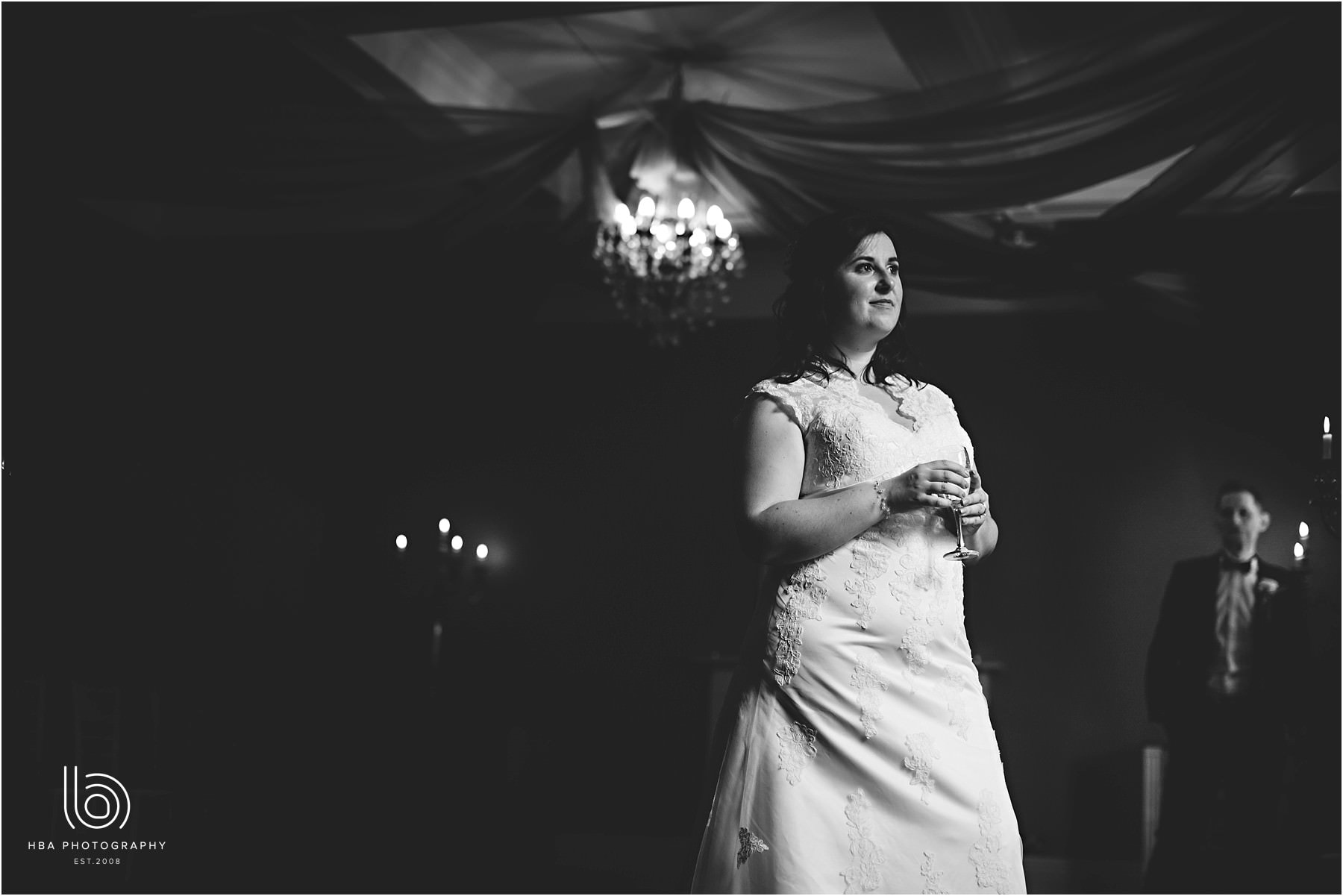 a black and white photo of the bride looking out of the window