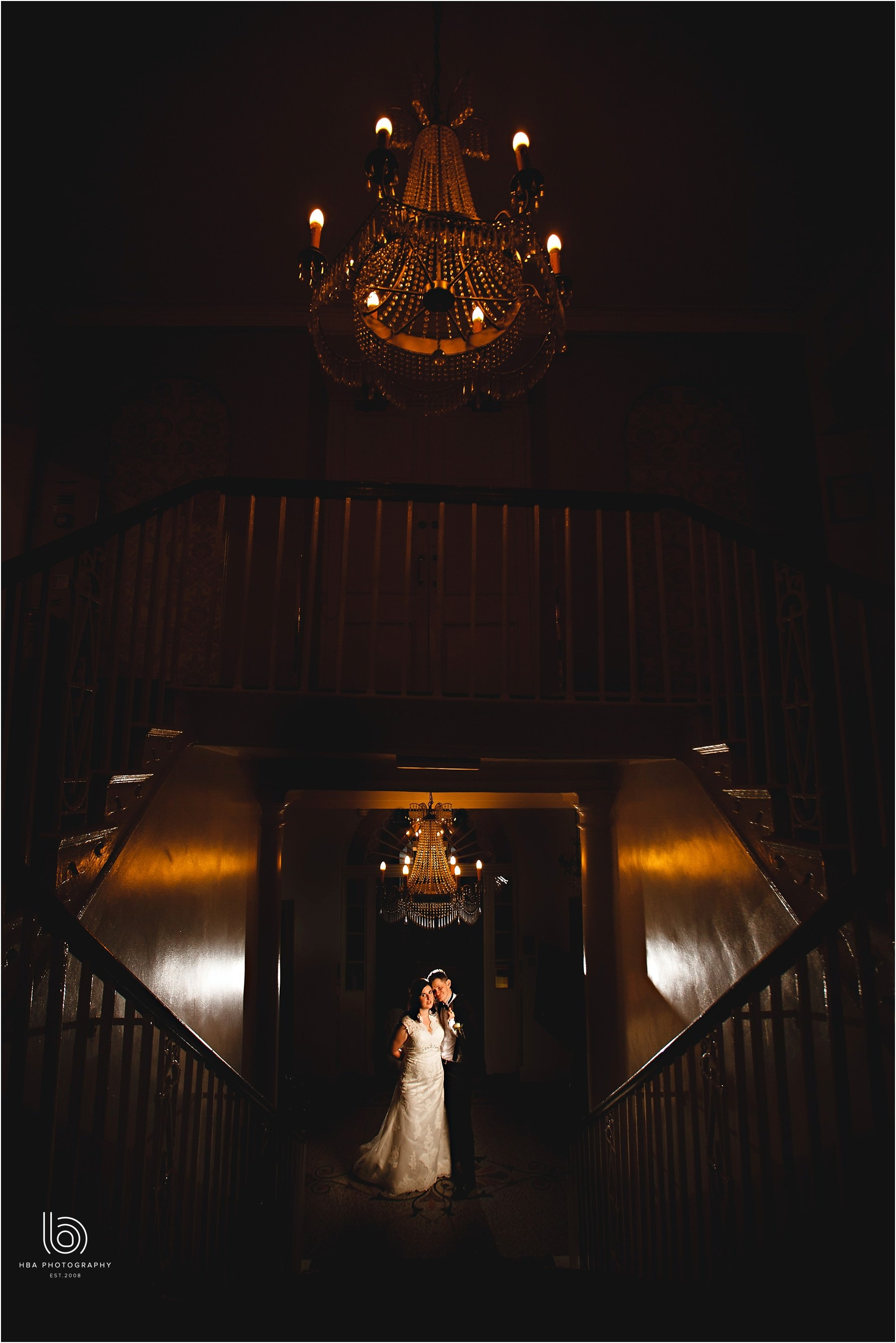 a dark photo of the bride and groom stood in orange lights in the hotel reception