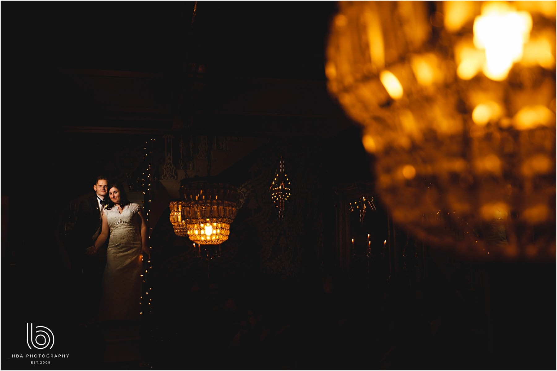 the bride and groom surrounded by big orange lights