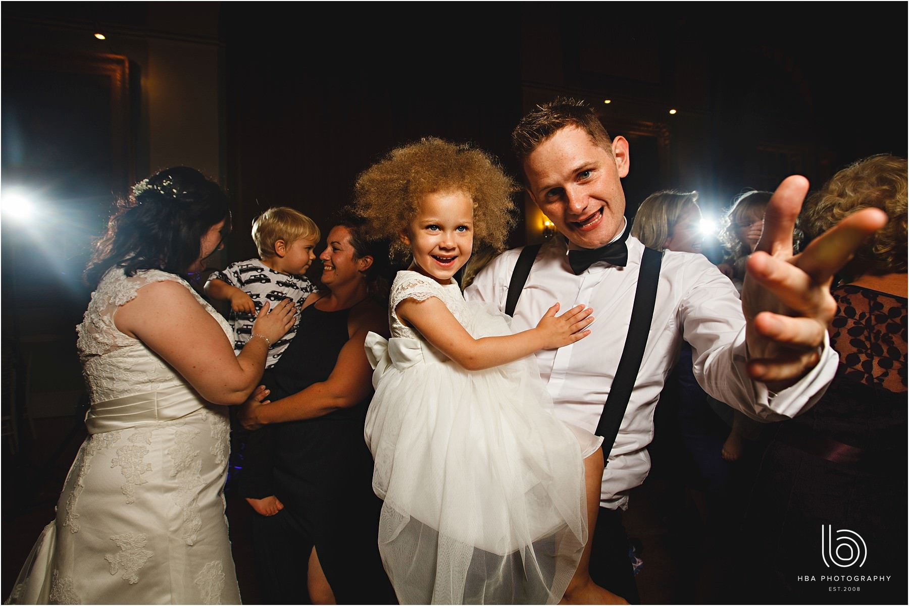 the groom with braces holding a little girl on the dance floor