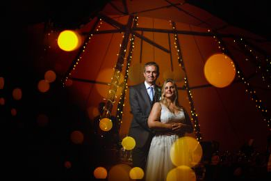 the bride and groom stood in twinkle lights in the tipi