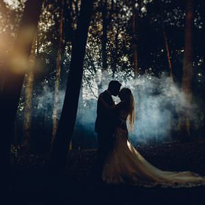 the bride and groom in the woods at Osmaston park surrounded by smoke