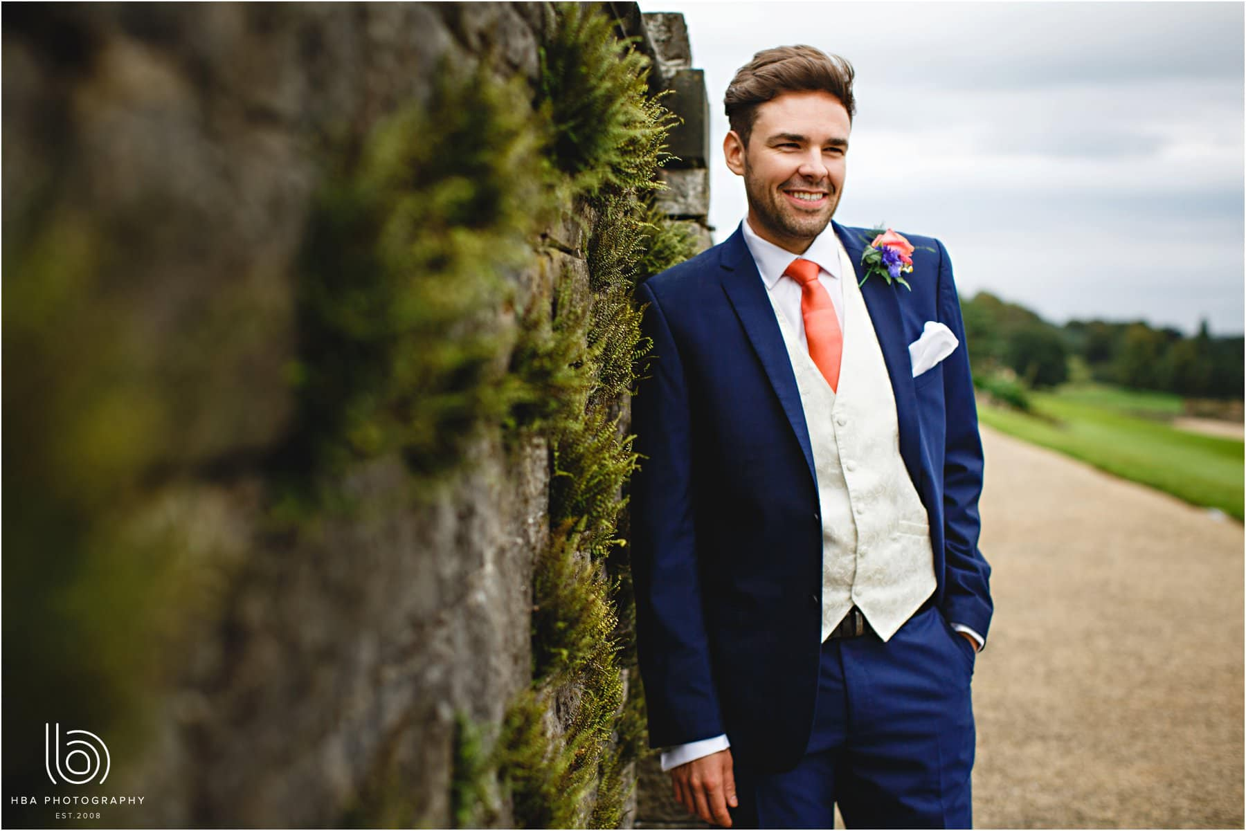 the groom leaning against a wall