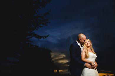 The bride and groom stood in darkness with the sun setting behind them
