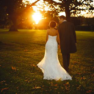The bride and groom in the grounds at Swinfen Hall walking into the sunset