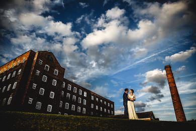 the bride and groom stood in the sunshine at The West Mill in Derbyshire