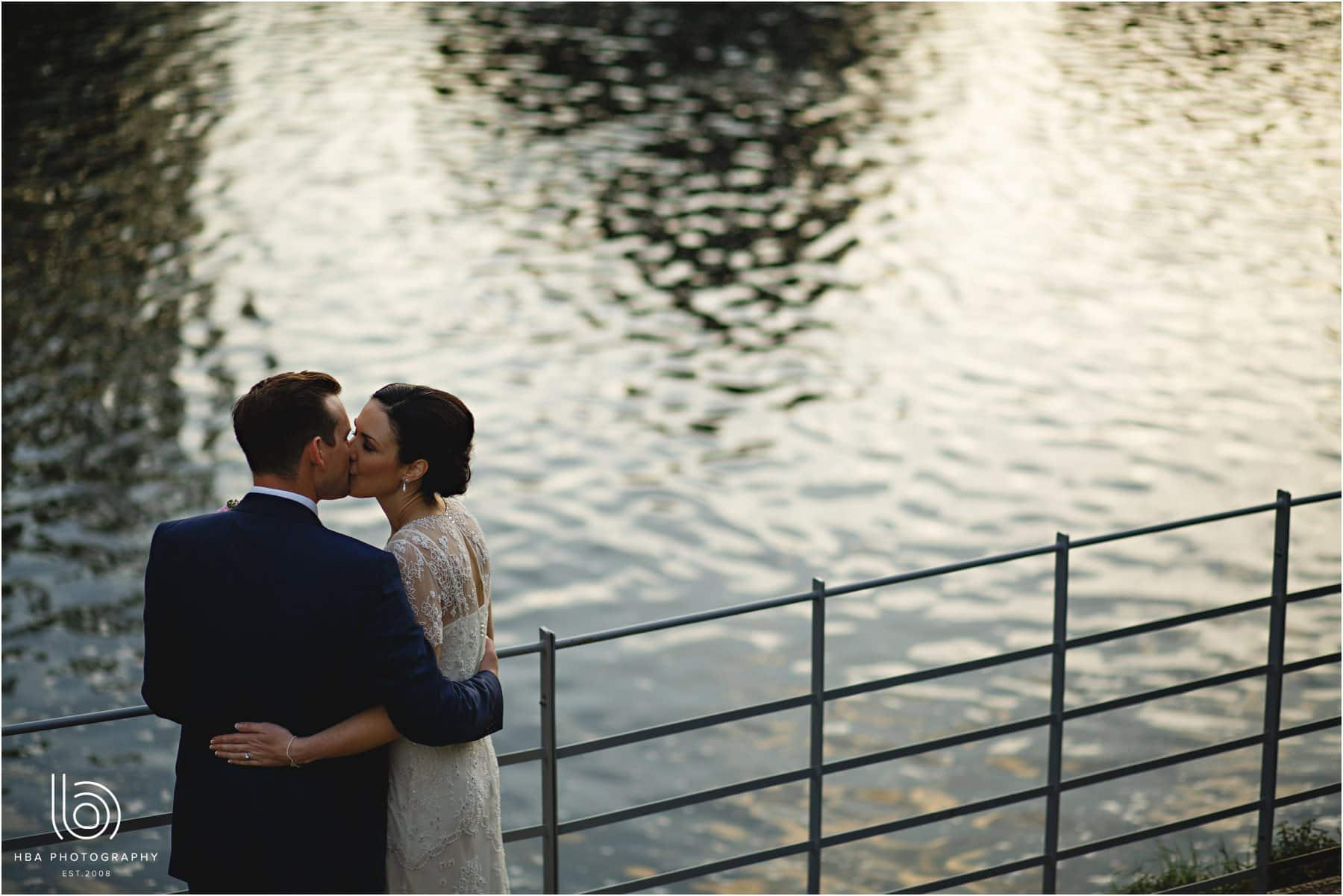 the bride & groom by the river at the west mill