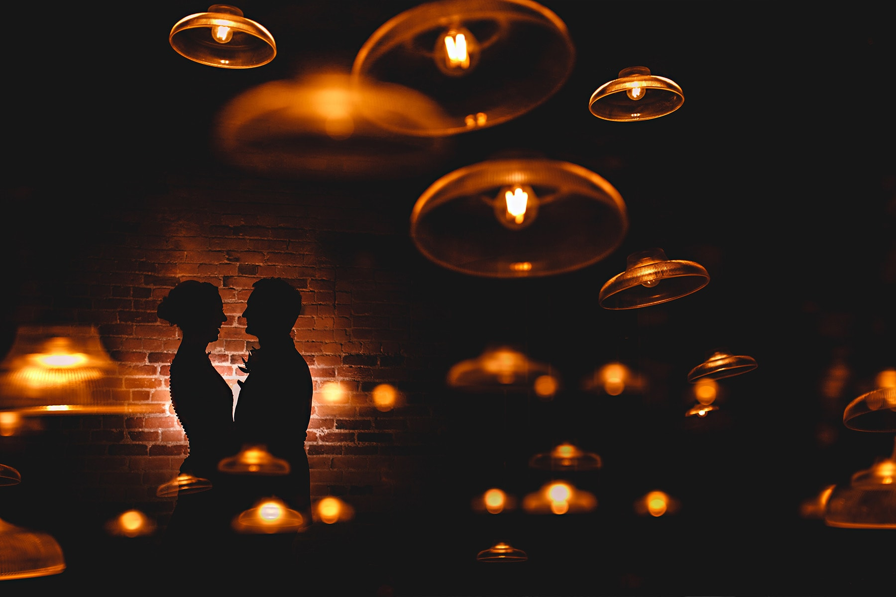 West Mill wedding photo of the bride and groom stood in orange lights
