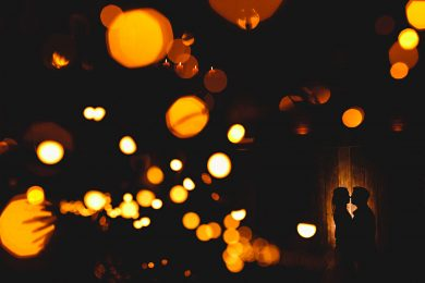 the bride and groom stood in orange lights