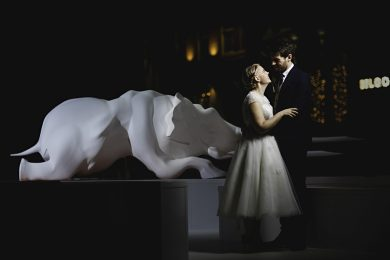 the bride and groom stood in an art exhibition next to a white elephant