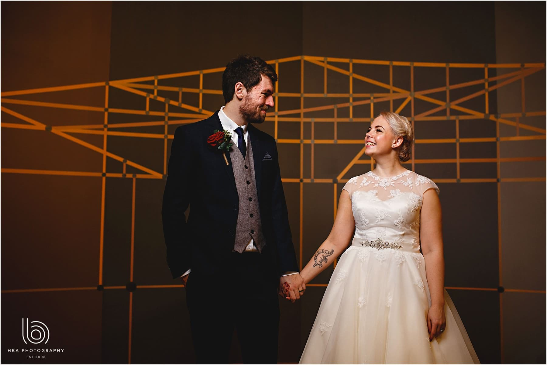 The bride and groom stood next to a geometric wall pattern in orange