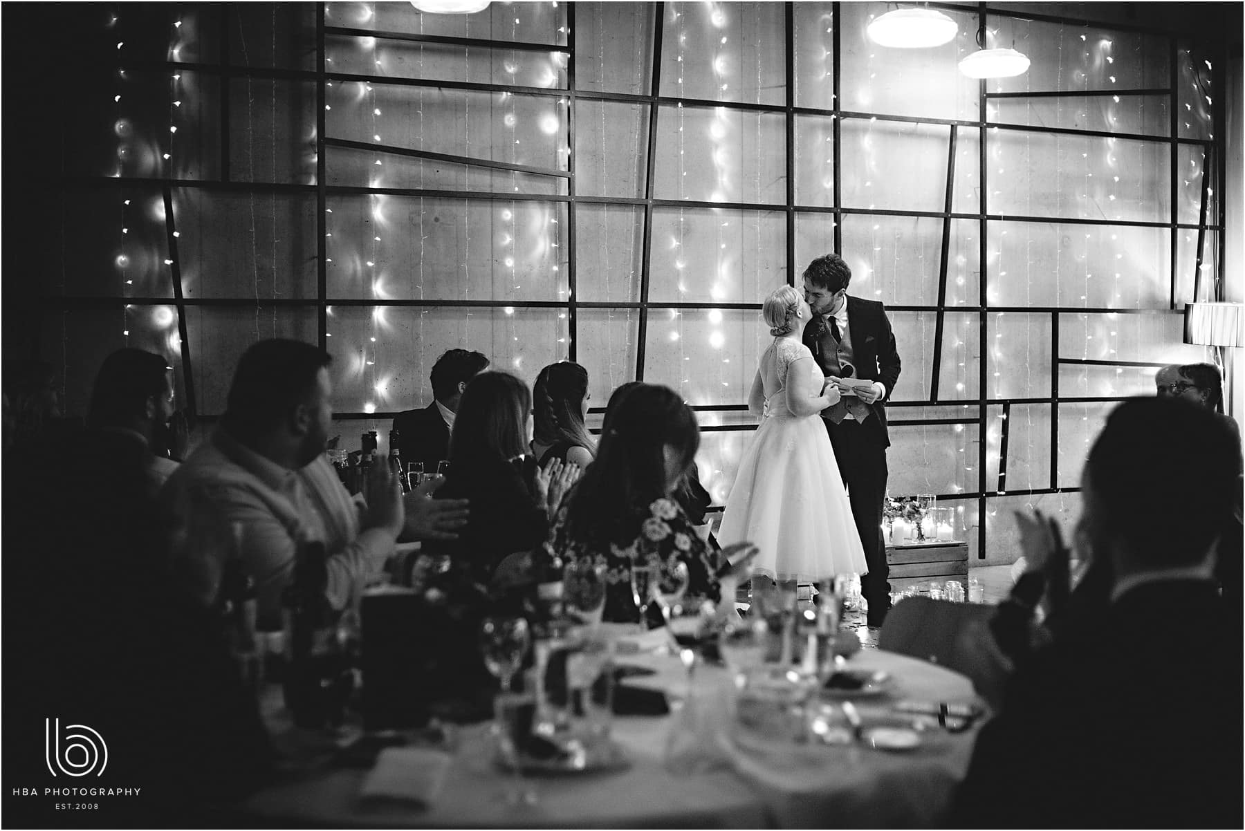 The bride and groom kissing during their wedding speech in black-and-white
