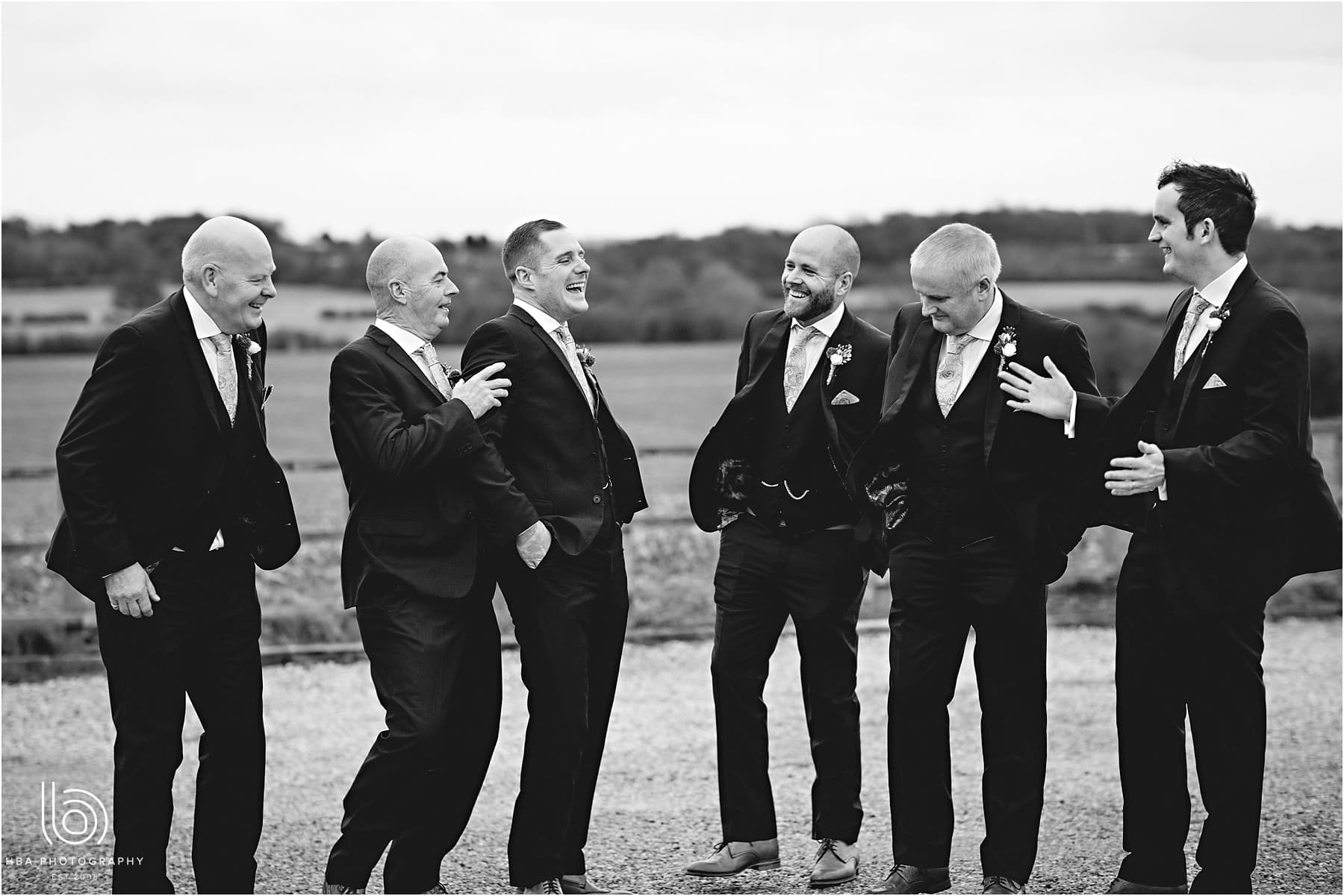 A black-and-white photo of the groomsmen laughing