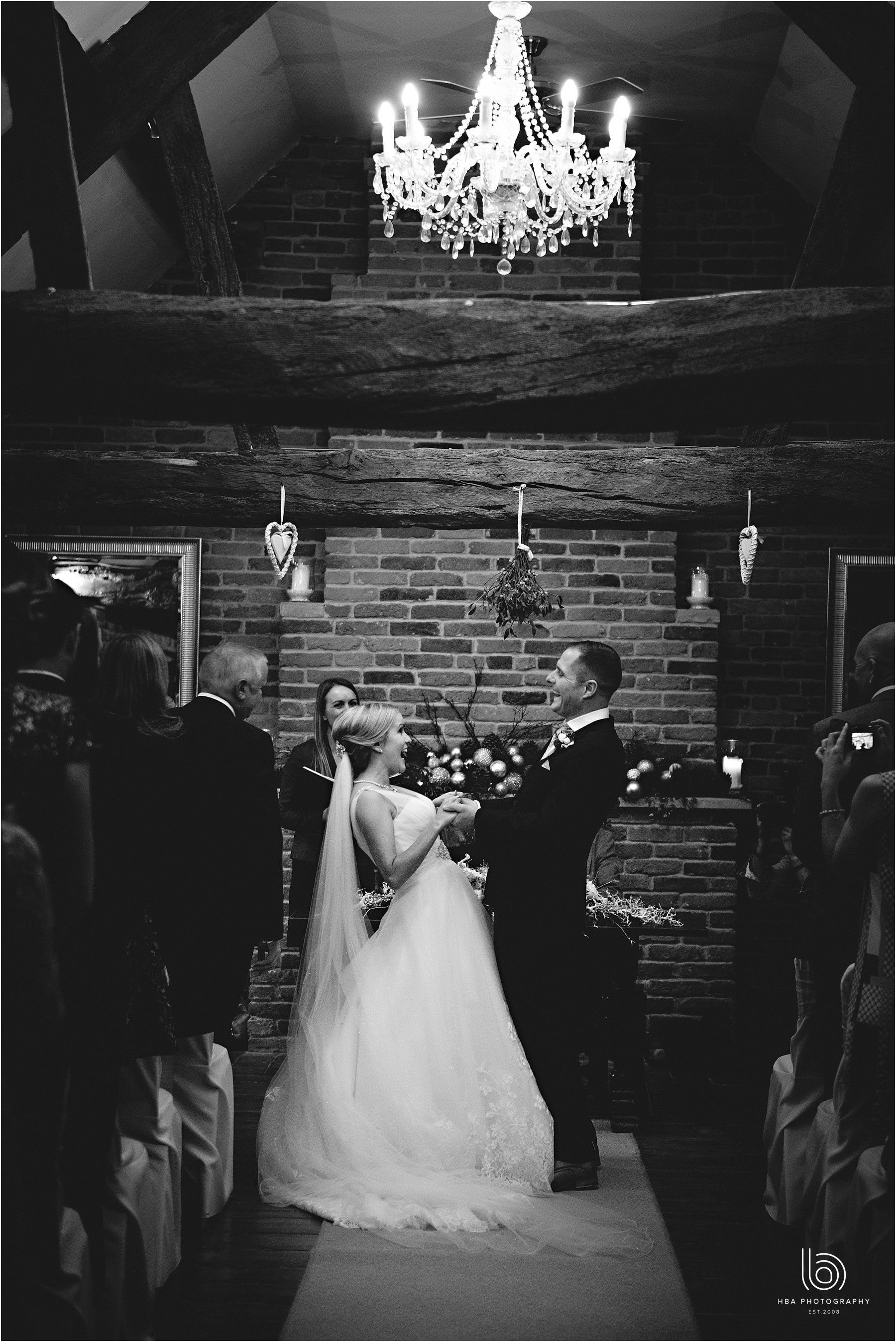 the bride and groom holding hands laughing at each other in black-and-white