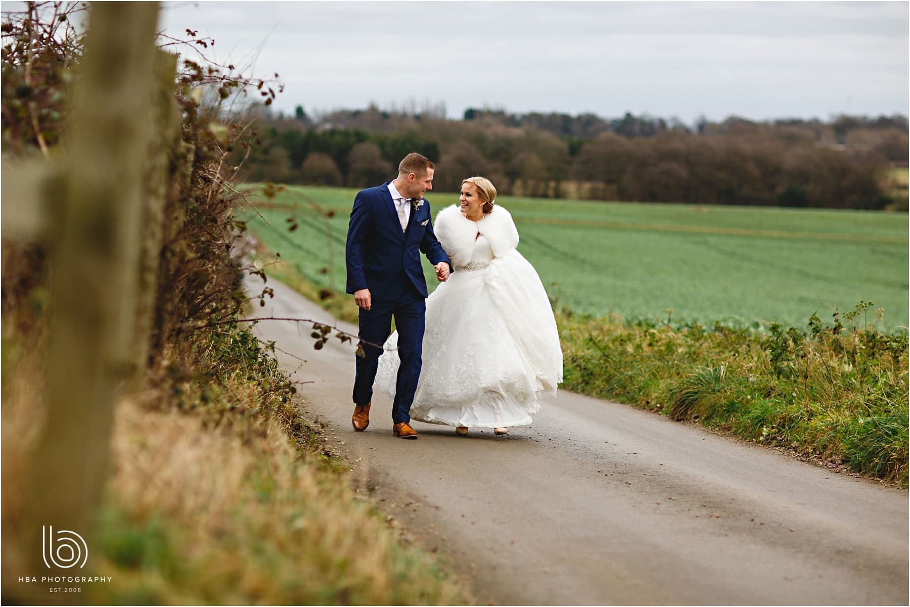 The bride and groom walking in the countryside at Swancar Farm Country House in Nottinghamshire