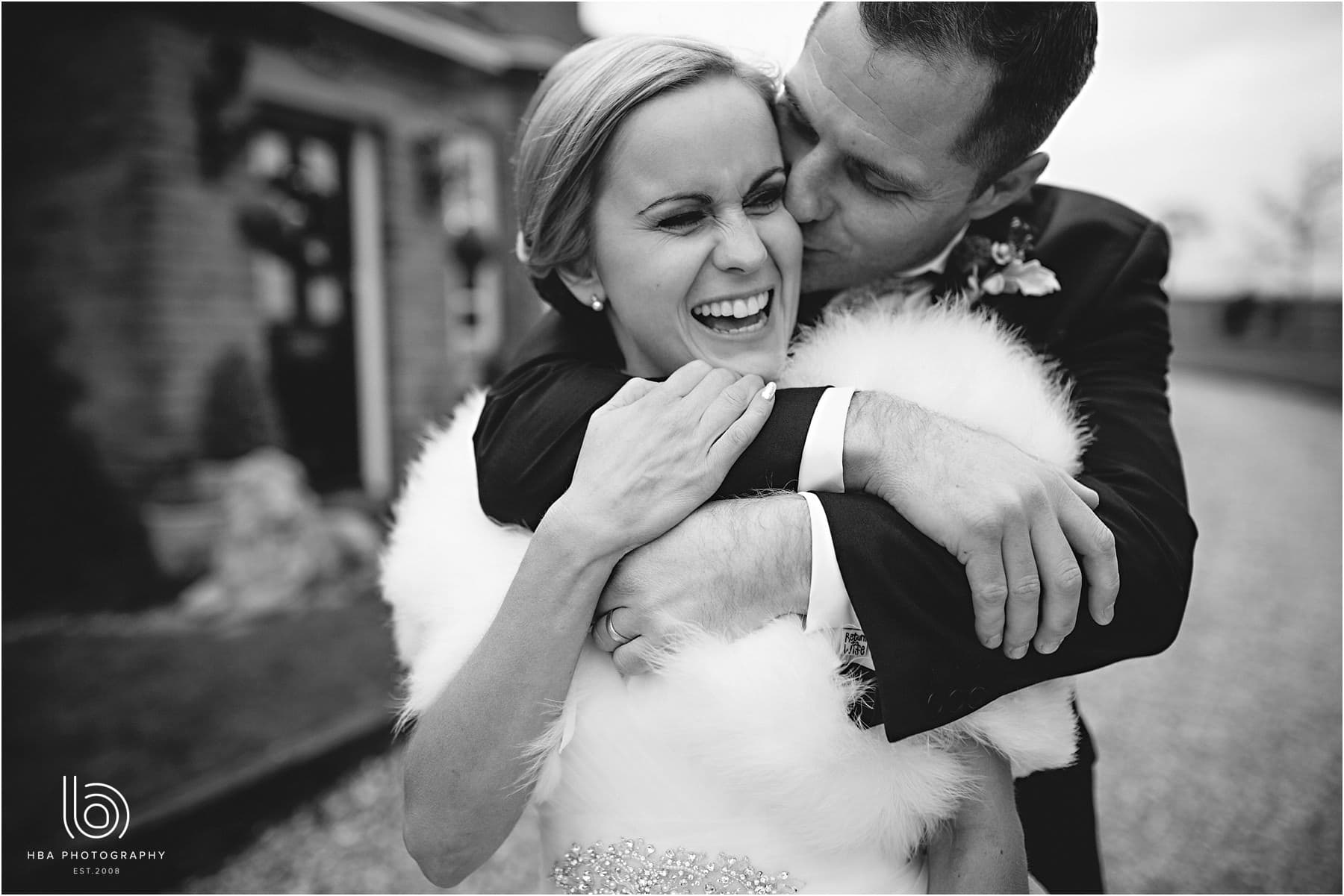 The bride and groom hugging each other laughing in black-and-white