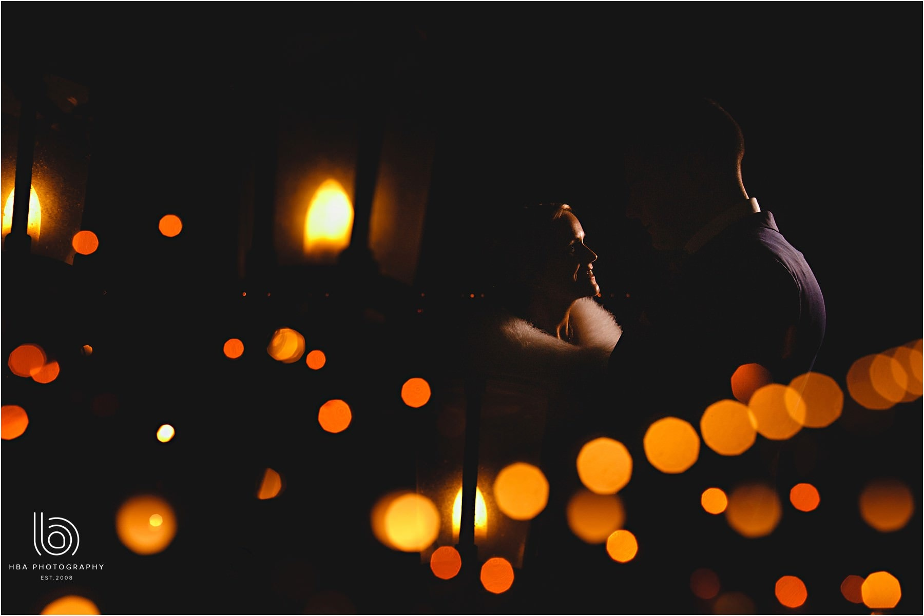 The bride and groom in the dark surrounded by orange lights