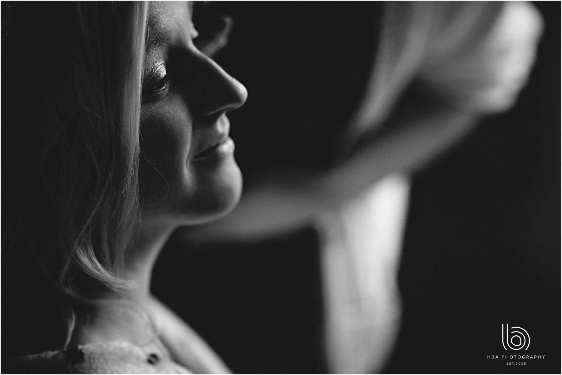 A black and white photo of the bride is having her make up done