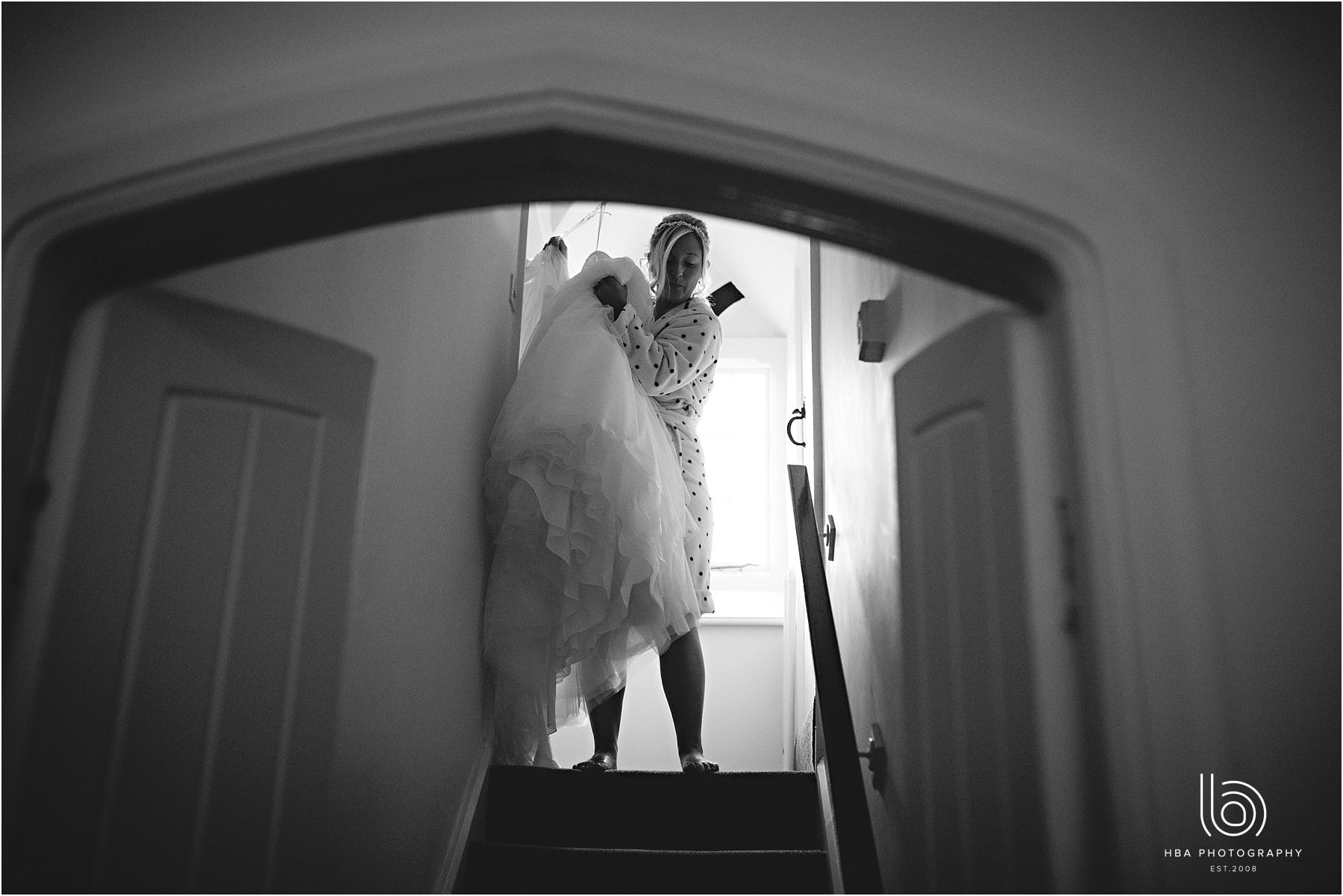 The bride carrying her wedding dress down the stairs