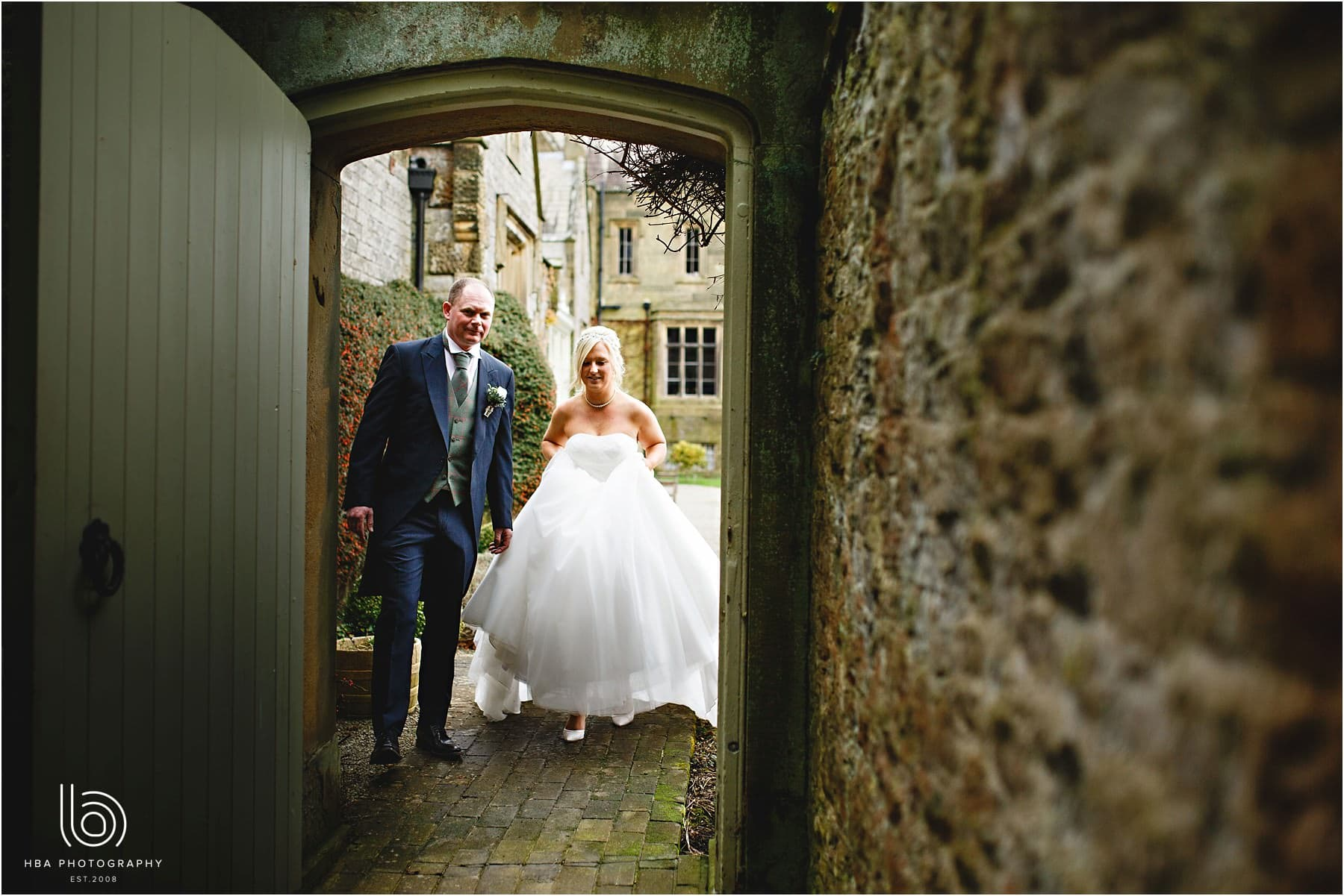 The bride and groom walking through an archway