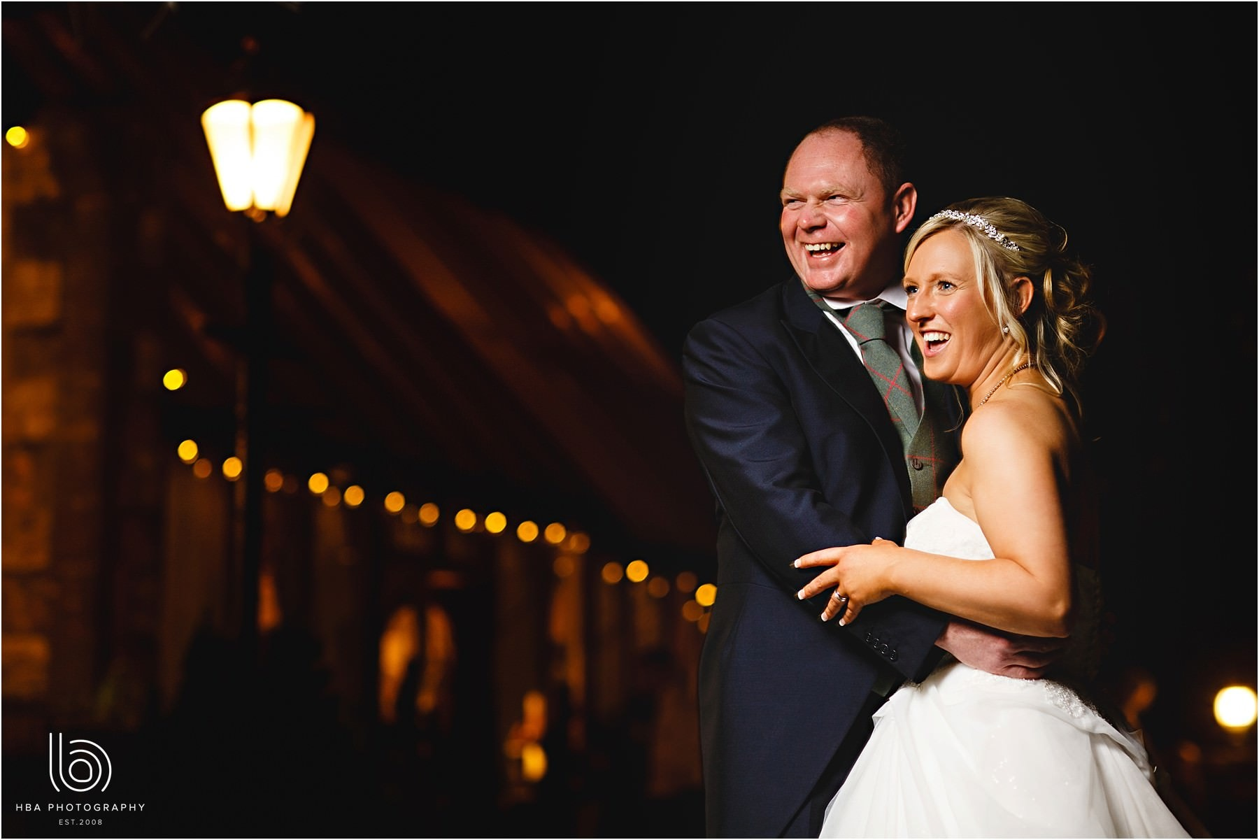 The bride and groom outside at night surrounded by orange lights