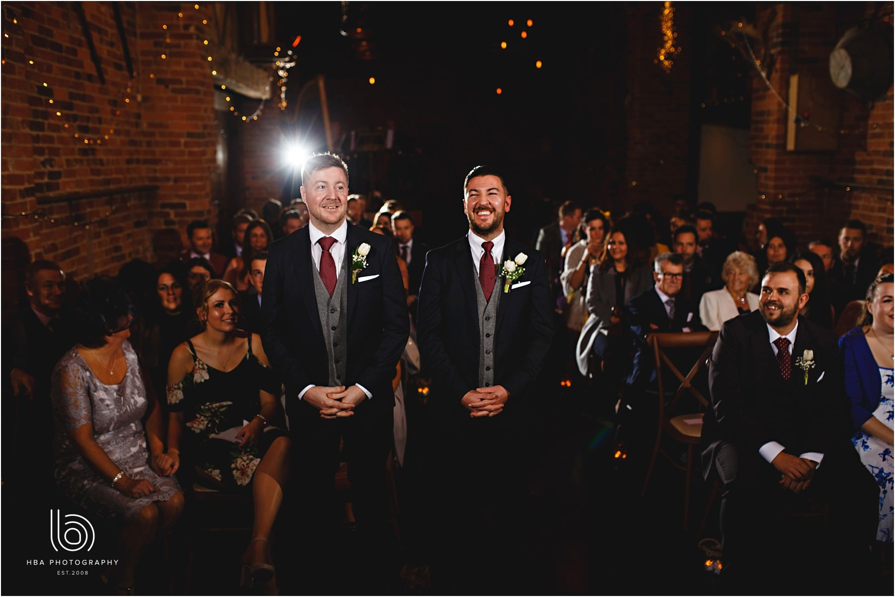 The groom and his best man waiting at the front of the aisle