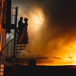 the bride and groom stood in orange sunlight