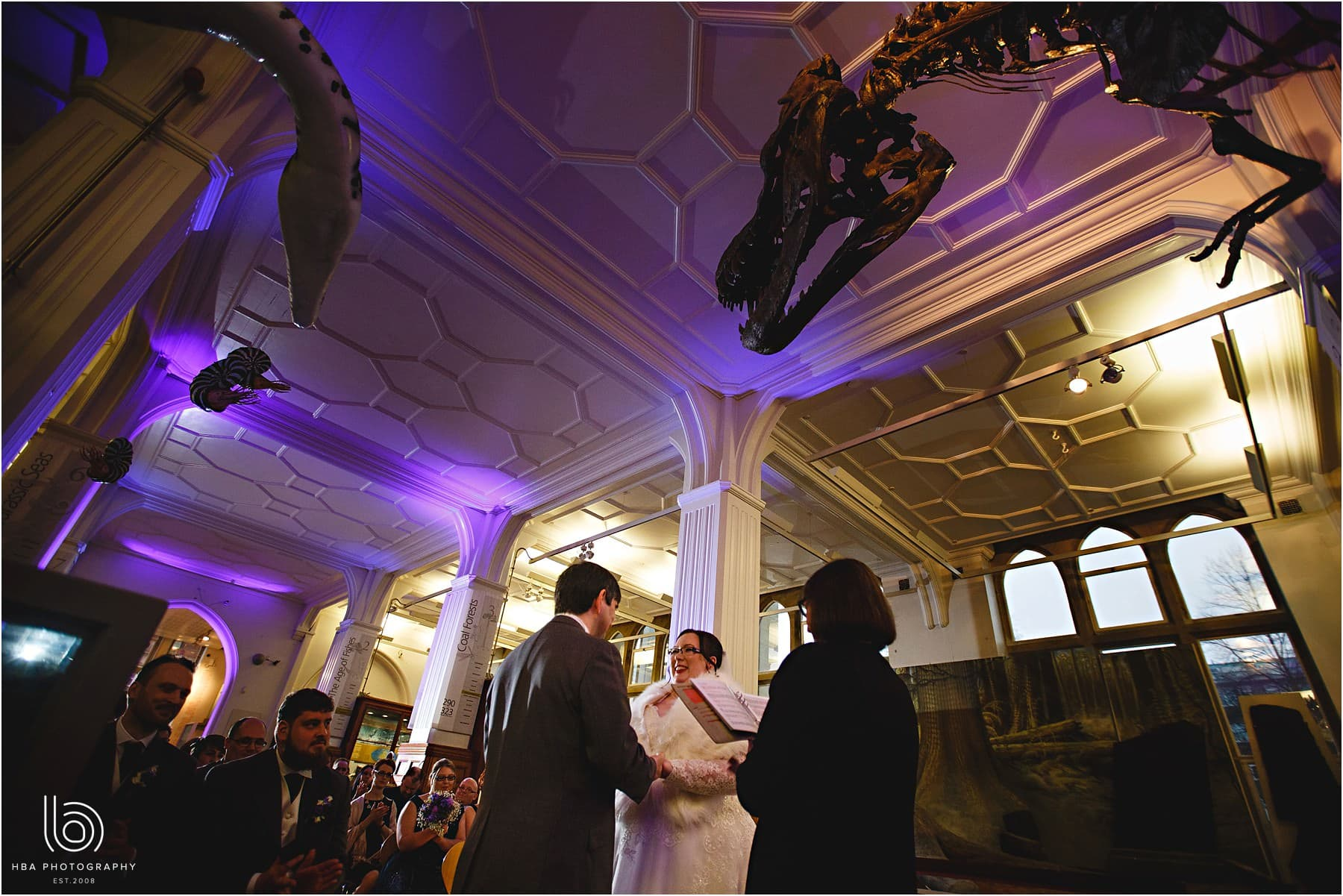 the bride & groom getting married under the T-Rex