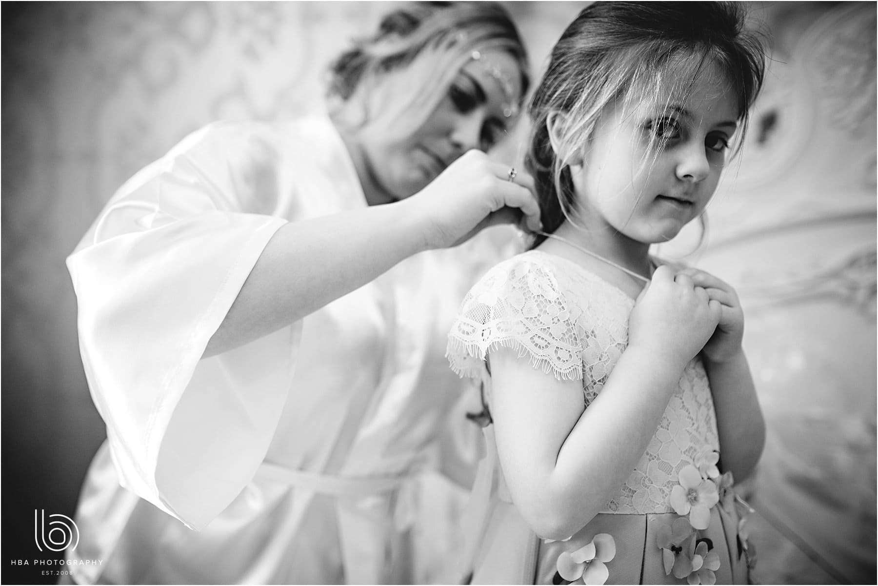 the flower girl getting her necklace on