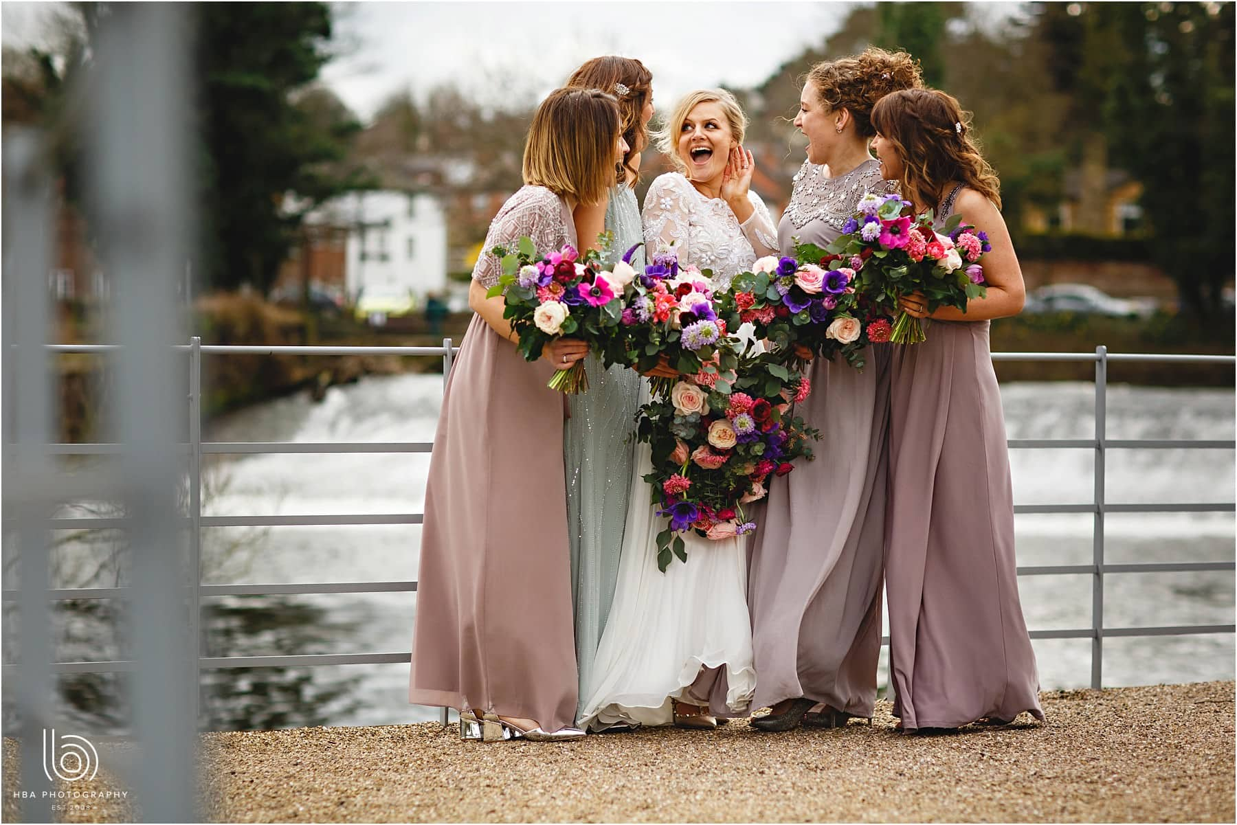 the bride and her bridesmaids by the river