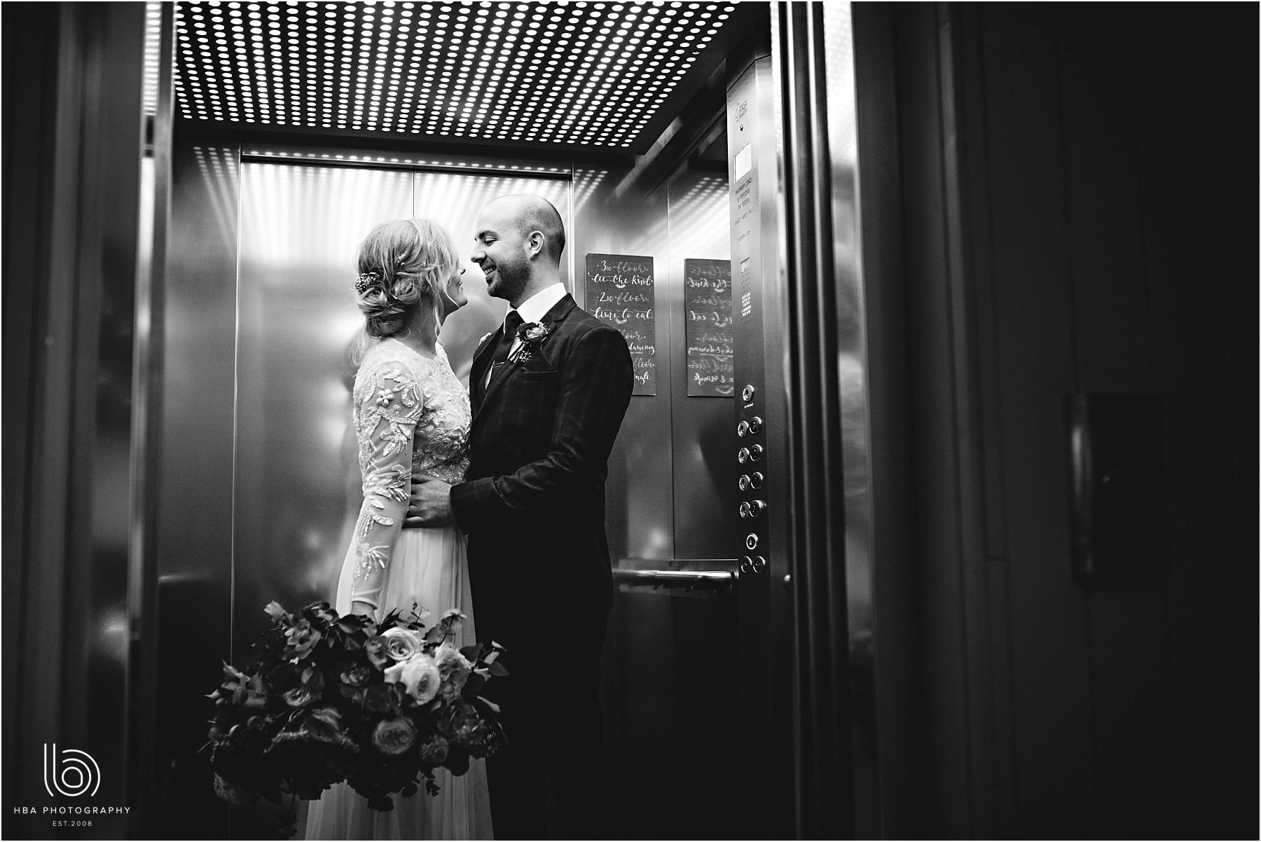 the bride & groom in the lift at the west mill