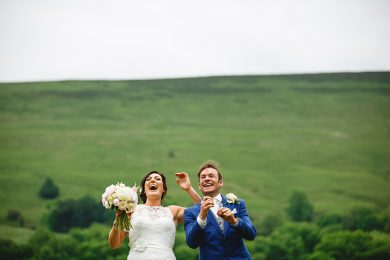 the bride and groom laughing with the green hills in the background
